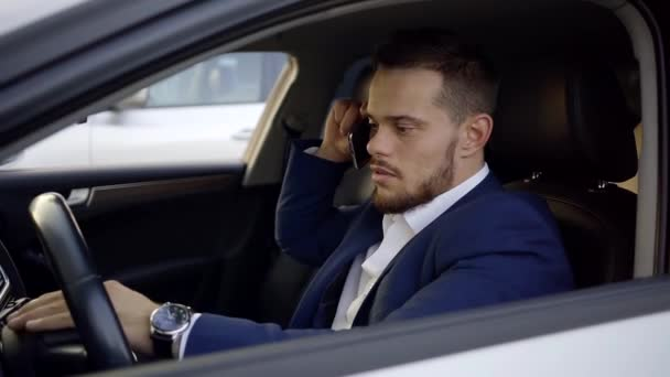 Young and handsome businessman talks on the phone and makes deals sitting in expensive car.