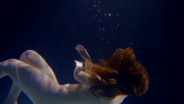 Charming woman is floating naked underwater,