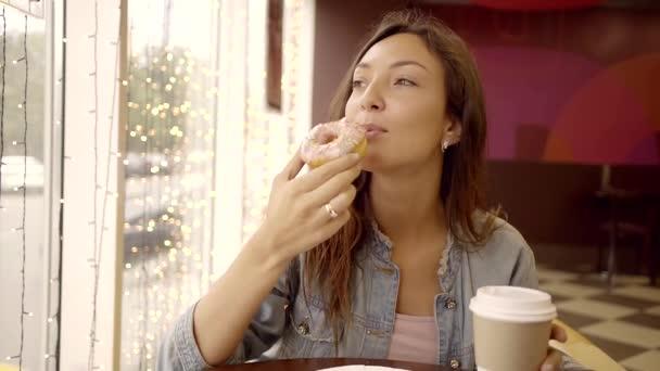 fröhliche Frau isst süßen Donut und trinkt Kaffee im Café.