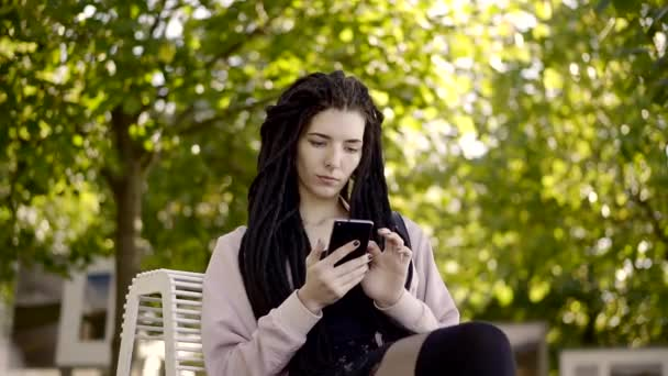 Mladá žena s dredy na hlavě, komunikovat s přáteli na smartphone v parku