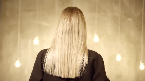 Rückansicht der langen Haare einer Frau, die ihren Mantel auszieht, unter ihrer Kleidung ist ein nackter Körper