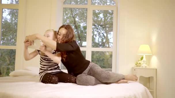 Aranyos nő időt tölt a lányával, az ágyban, a lányok próbálnak, hogy másik tabletta
