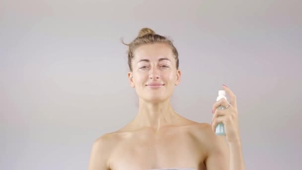 A young woman applies a moisturizing spray on clean skin of the face and body, then massages the head