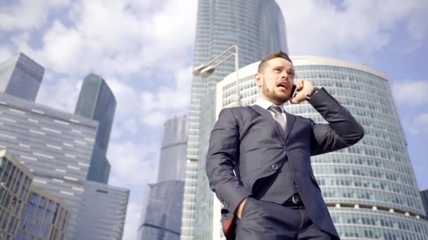 Mladý a pohledný muž, který vypadá jako podnikatel, hovoří o mobilním telefonem s přímou volbou s investory na pozadí obchodní budova
