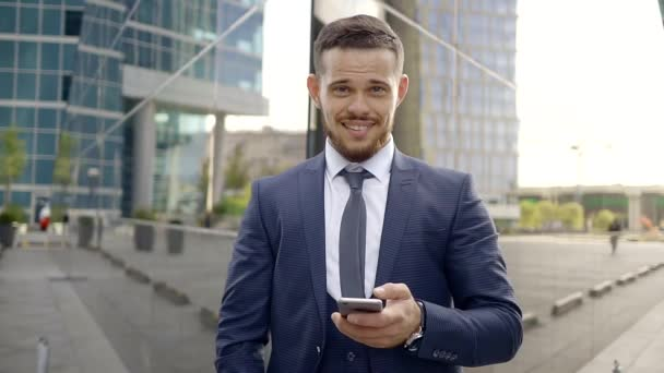 An attractive man, maybe a businessman or manager, is holding a mobile phone in his hand and laughing