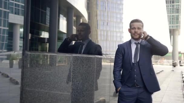 Egy fiatal és komoly ember, aki úgy néz ki, mint egy vállalkozó, beszél a telefonon, a befektetők közelében az irodaház