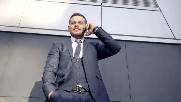 Přemýšlivý člověk poslouchá hlas svého obchodního partnera, který mu volal na svůj mobilní telefon