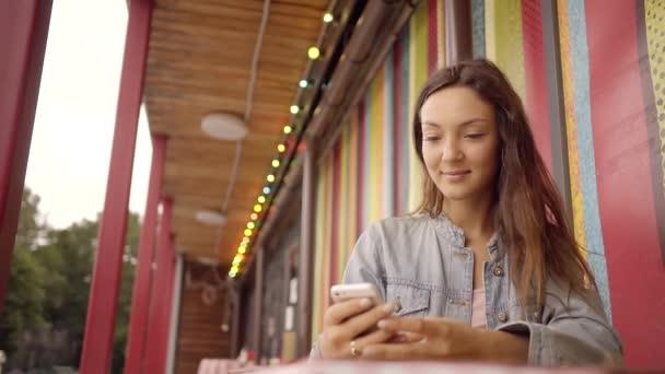 eine hübsche Frau hält ein Handy in der Hand und kommuniziert mit Freunden in sozialen Netzwerken auf einem Smartphone