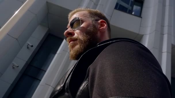 slow motion. 500 frames second. stylish man with a beard in sunglasses. clothes from modern materials eco leather. straps and rivets.