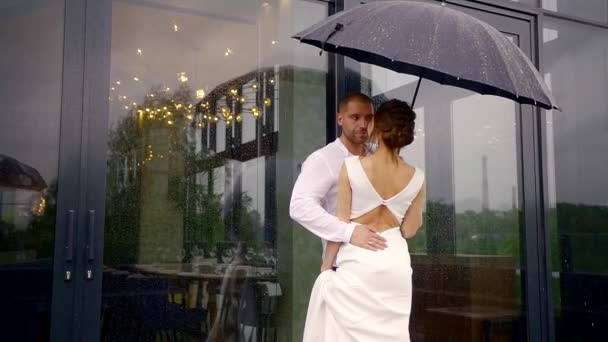 a man and his beautiful bride dressed in a white wedding dress are standing together under an umbrella, its raining outside, and the newlyweds are hugging and talking to each other