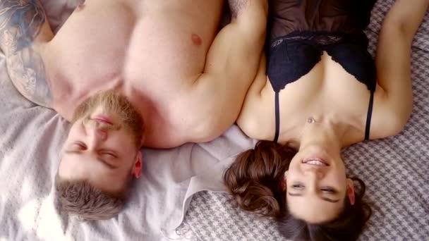 junge Frau in Unterwäsche liegt neben ihrem Mann, Paar lacht und lacht auf dem Bett liegend