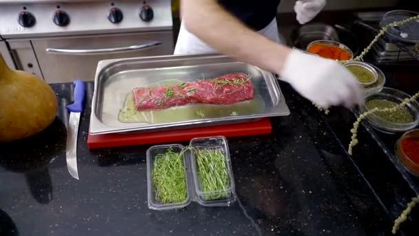 kuchař připravuje hovězí svíčková pro vaření. namažte olejem, posypte solí a kořením