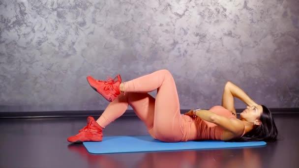fitness trenér ukazuje výkon kroucení nohu jedince na váze. cíl svalové skupiny tisk