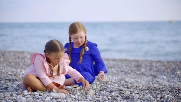 Children spending time sitting on the beach playing with pebbles.