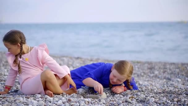 Two silly kids playing on the shore with pebbles in the evening.