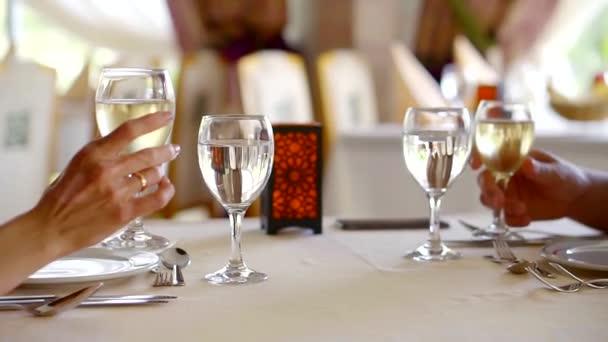 Boční pohled záběr pár dělat na přípitek v restauraci držení sklenice s bílým vínem