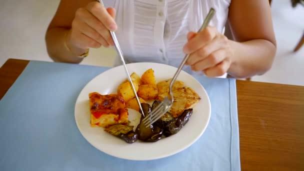 Detailní záběr záběr ženy jíst dobré chutné jídlo s vidličkou a nožem v restauraci