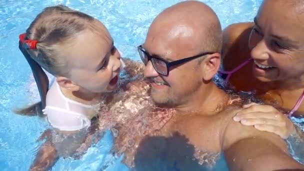 Close up shot of a happy family of three daughter mother and father spending time in a pool.