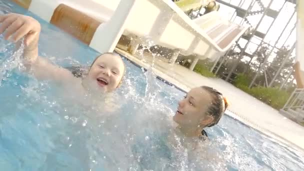 Two sisters having a fun holidays in the pool with big water slide.