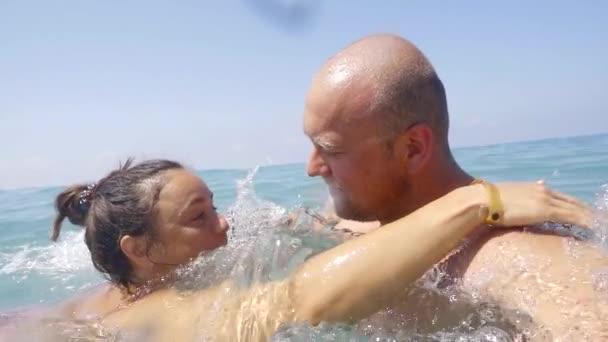 Manžel sdílí polibek se svou ženou v moři.