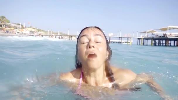 Detailní záběr záběr ženy stojící v moři a dělat hloupé ksichty.