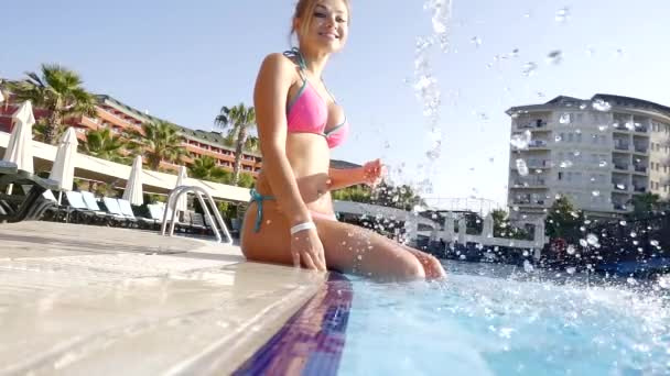 Beautiful fit woman is sitting on the edge of outdoor hotel pool with her legs in water.
