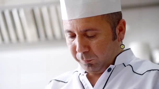 Porträt von einem professionellen Koch arbeitet in einer Restaurantküche in weißer Uniform hautnah
