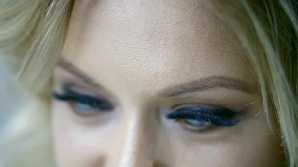 close-up view of beautiful female blue eyes with vivid makeup and fake lashes, woman is looking at camera and down