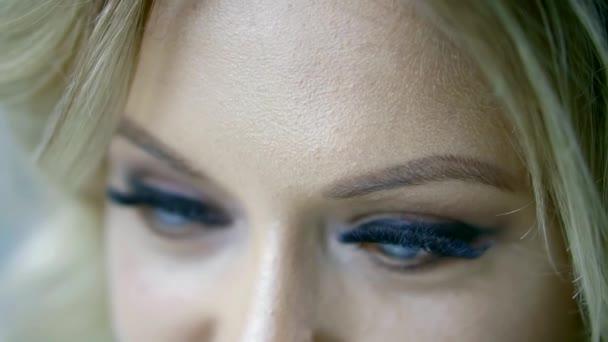 Detailní pohled krásné ženské modré oči s živými make-up a falešné řasy, Žena se dívá na kameru a dolů