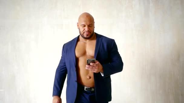 Pohledný muž v saku obleku s nahý trup chůze vpřed a držení smartphone.