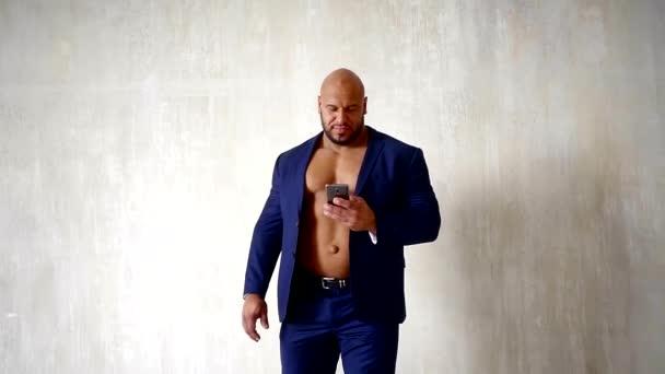 powerlifter muž má na sobě modrý oblek na nahou hruď chodí v místnosti a při pohledu na displeji svého mobilního telefonu