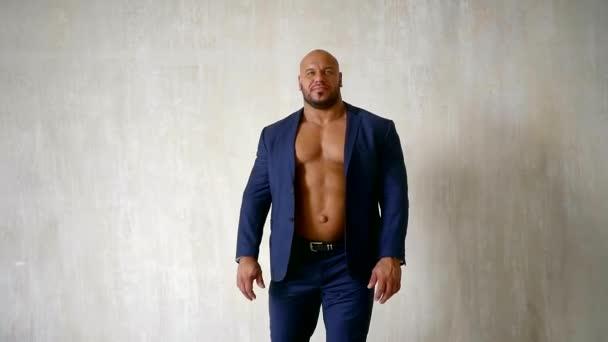 jistý kulturista oblečený luxusní modré barvy s rozepnutou bundou, prokazující nahé hrudi