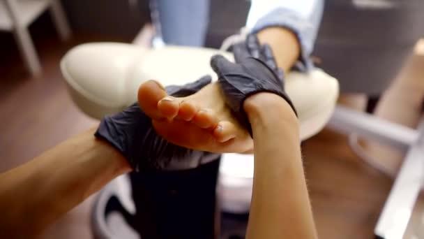 Maestro è massaggiare un piede del cliente femminile in un salone di bellezza durante la procedura di pedicure