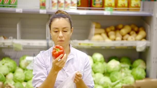 Detailní záběr záběr krásná bruneta žena výběr čerstvé červené papriky v obchodě