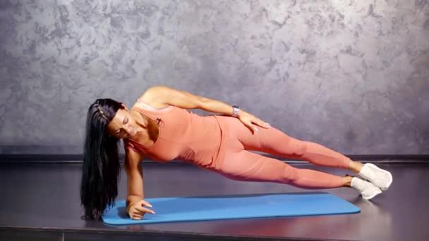 Krásná bruneta fitness trenér dělá boční prkna na mat pro jádro