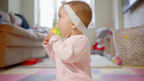 Close up shot of a cute baby wearing lovely pink suit and white band on the head playing and biting a toy.