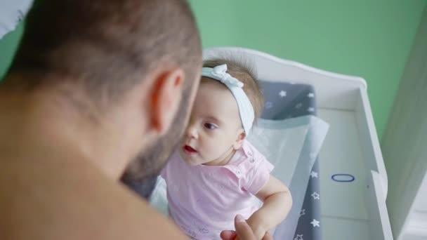 Close up shot of a beautiful infant girl looking up at her father from bed and smiling.