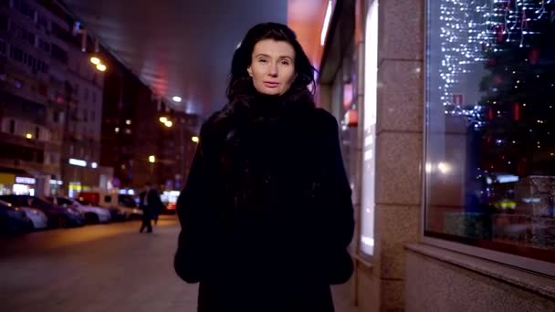 Elegant middle-aged woman walks on a cold winter evening along the storefronts of the shopping center
