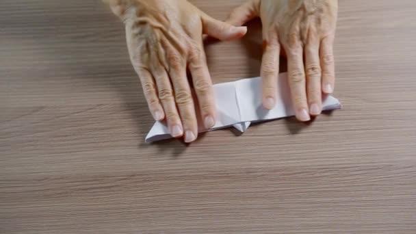 zblízka. žena ruce úhledně složené z listu dokumentu white paper model lodi