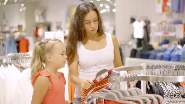 mother and her child girl are watching on a hangers with clothing in a store, woman is taking items