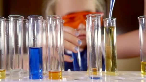 ragazza del bambino sta eseguendo esperimenti di chimica con i liquidi in un reagente di laboratorio da solo, gocciolante