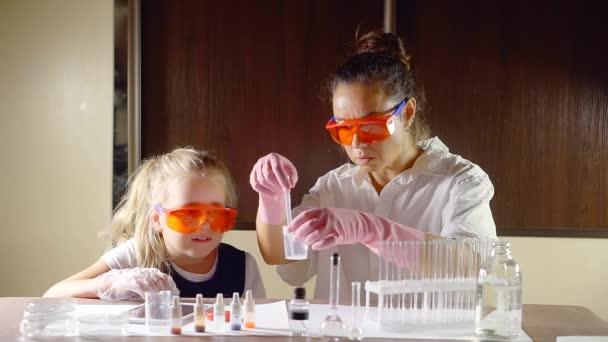 pro dospělé bruneta žena a preschooler dívka se učí chemická reakce v lahvičce s kapalinami