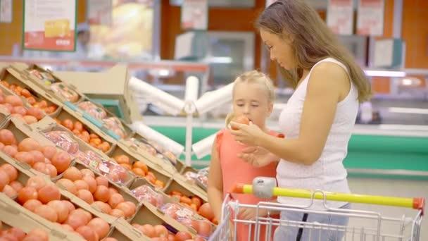 Krásná bruneta žena a malá blondýna dívky výběr čerstvé zeleniny.