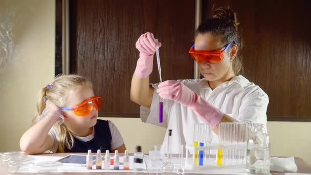 adult mother is showing to her small child daughter chemical reaction in a glass vial, little girl is amazing and smiling, play together