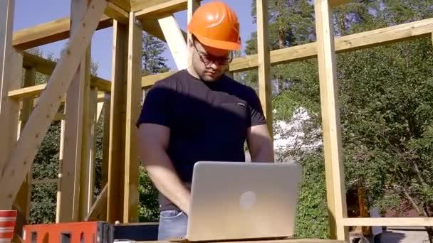Engineer in helmets, laptop computer, inside the building under construction.