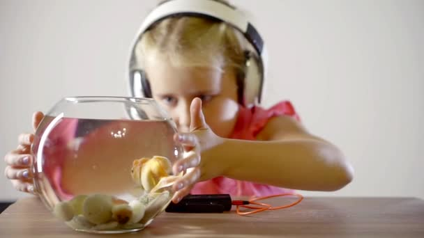 little baby girl playing with aquarium fish looking at fish swimming in the aquarium. listen to music with headphones
