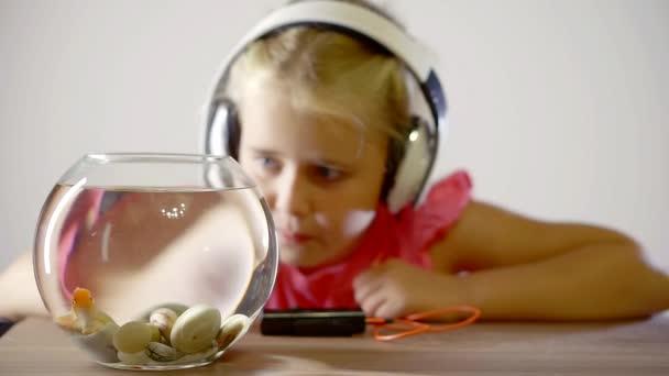 Roztomilá holčička se sluchátky a ryby v akváriu