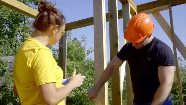 Male and female workers building a house.