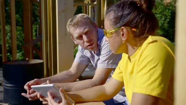 Weibliche Bauherr und Auftragnehmer reden auf dem Gelände im Sommer.