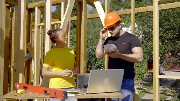 muž a žena stavitelé jednají v době přestávky na pracovní místo ve staveniště v slunečný den